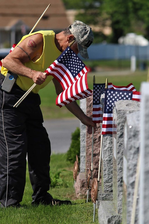. Army veteran Paul Renda puts a flag on a veterans grave at Forest Hill Cemetery on Thursday afternoon. SENTINEL & ENTERPRISE/JOHN LOVE