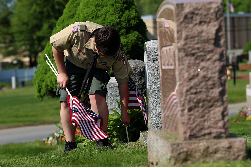 Troop 41 Boy Scout Patrick McWalter puts a flag on a veterans grave at Forest Hill Cemetery on Thursday afternoon. SENTINEL & ENTERPRISE/JOHN LOVE