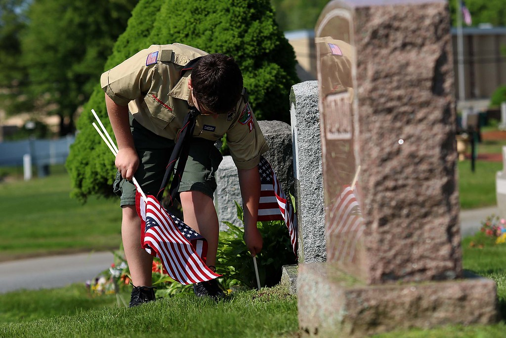 . Troop 41 Boy Scout Patrick McWalter puts a flag on a veterans grave at Forest Hill Cemetery on Thursday afternoon. SENTINEL & ENTERPRISE/JOHN LOVE