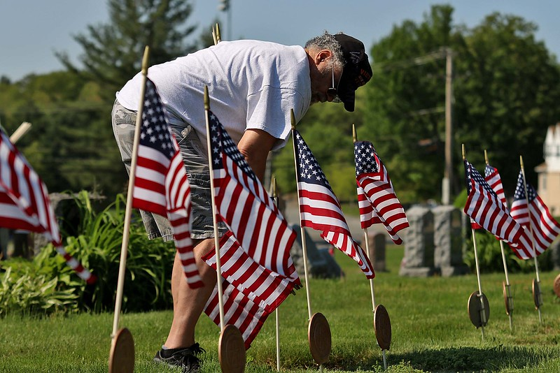 Vietnam veteran John Lyle puts a flag on a veterans grave at Forest Hill Cemetery on Thursday afternoon. SENTINEL & ENTERPRISE/JOHN LOVE