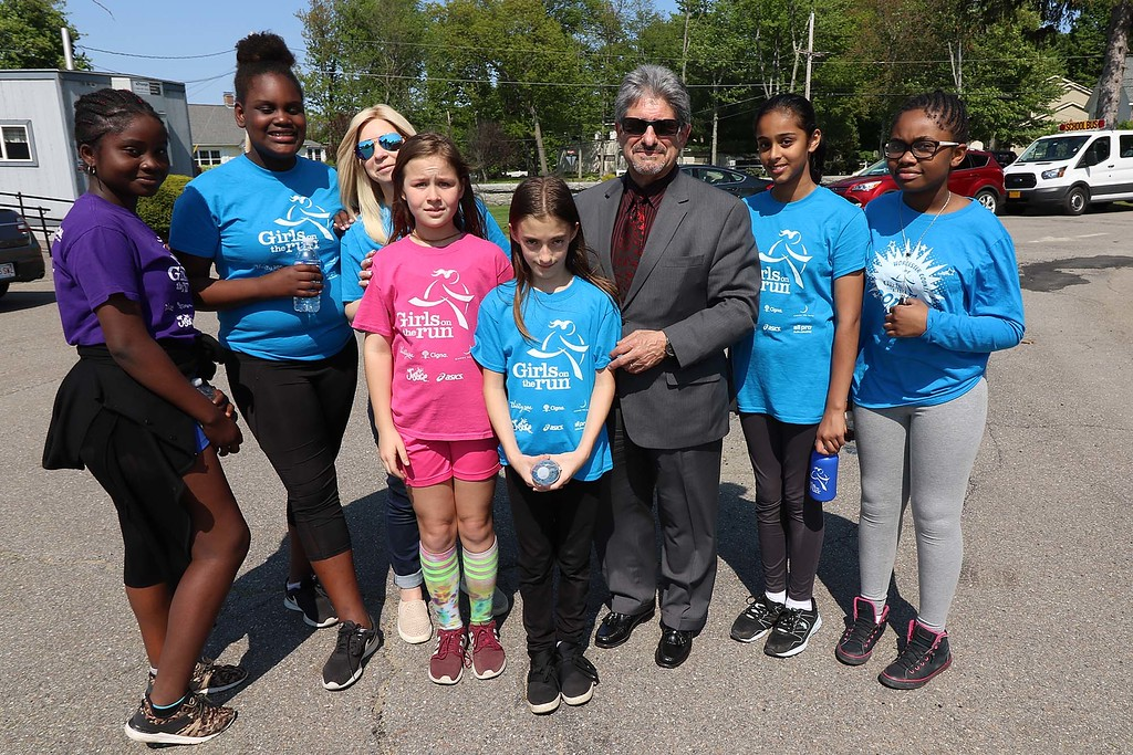 . Fitchburg Mayor Stephen DiNatale poses with students from the Memorial Middle School Girls on the Run program just before they went out to put flags on veterans graves. From left is students Faith Labah, Adriana Sanatana Novas,  Teacher Christen Sachse, students Athena William, Rebecca Palmer, DiNatale, Suha Waqar and Dominique Souffrant.  SETNINEL & ENTERPRISE/JOHN LOVE