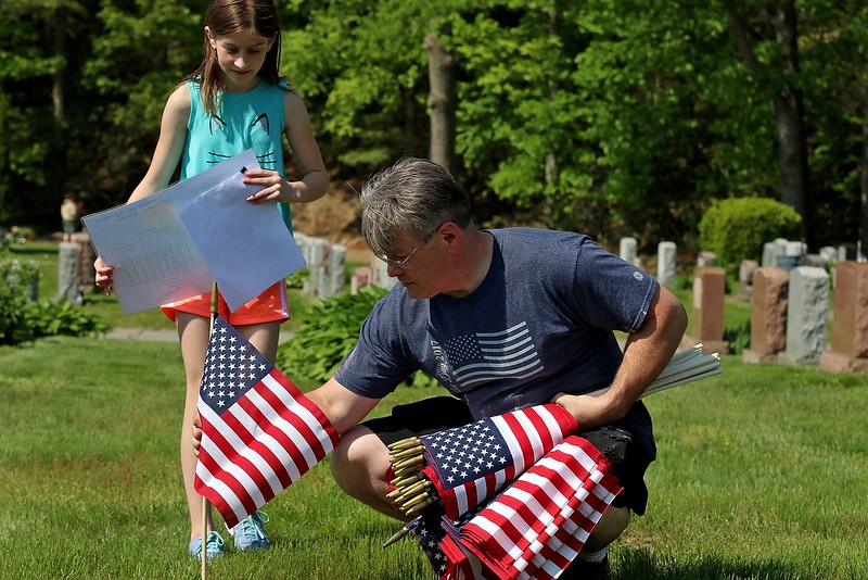 Charles Caron and his daughter Bella Caron, 12, work together to find the veterans grave so they could place a flag on them at Forest Hill Cemetery on Thursday afternoon. SENTINEL & ENTERPRISE/JOHN LOVE