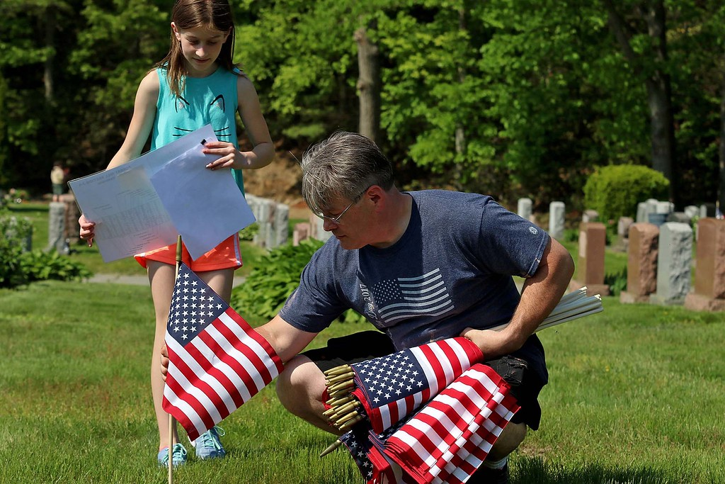 . Charles Caron and his daughter Bella Caron, 12, work together to find the veterans grave so they could place a flag on them at Forest Hill Cemetery on Thursday afternoon. SENTINEL & ENTERPRISE/JOHN LOVE