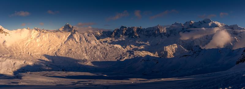 The setting sun illuminates the alpine panorama