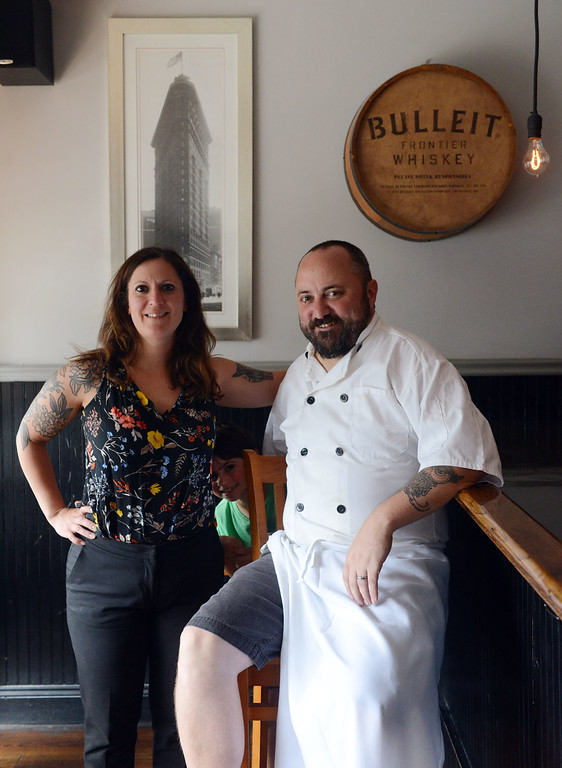 . Tania Barricklo-Daily Freeman    Flatiron co-owners Jessica Stingo and Craig Stafford.Their son Nathan Stafford,7, peeks out from between them.