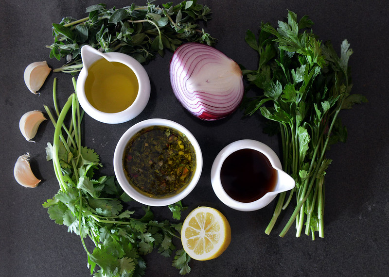 Tania Barricklo-Daily Freeman  Chimichurri sauce surrounded by its ingredients consisting of clockwise from top: oregano, red onion, italian parsley, sherry vinegar, lemon, cilantro, garlic and extra virgin olive oil.
