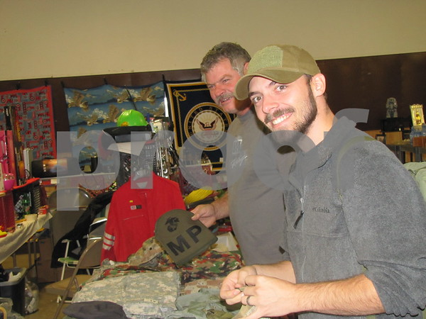 Nick Fleer (foreground) and Joe Peteson look over some of Fleer's army surplus.