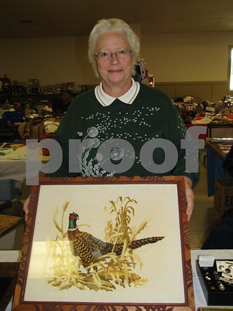 Donna Larson shows a hand-embroidered item from her booth.