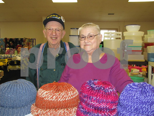 Russell and Marion Stamp in their booth at the flea market which features Marion's knitted hats and scarves, and fabric placemats.