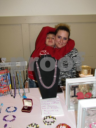 Robin Pate and son Zachary at her table featuring her handmade jewelry.