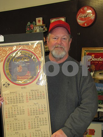 Mike Ryan with a Coca-Cola calendar from 1976 in his booth at the flea market.