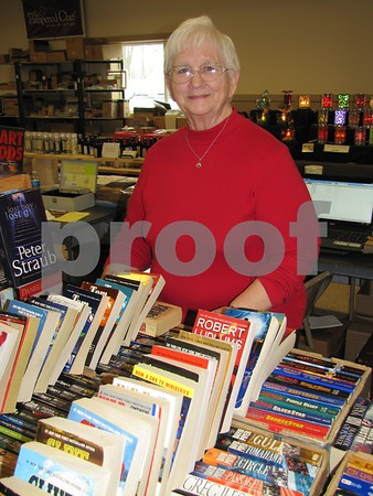 Martha Kohls (the book lady) stands next to her 15 foot? long table filled with books.