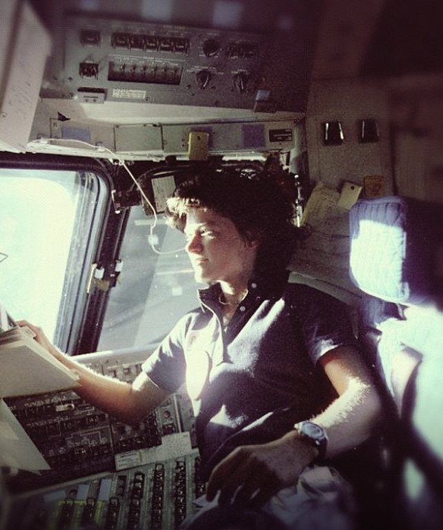 Sally K. Ride, sitting the pilot chair of a space craft.