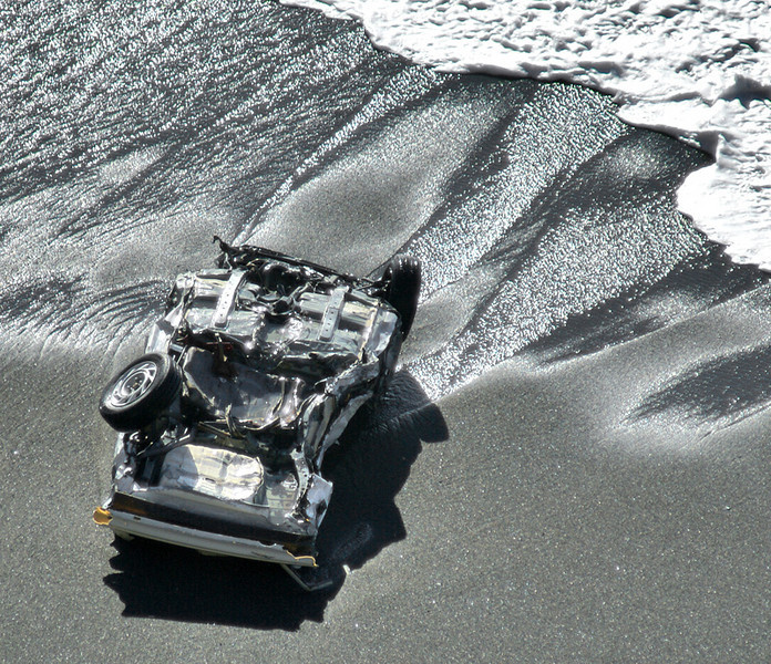 """Overturned auto on the beach  The reason for all the action at Mussel Rock in Daly City. A fellow photographer told me he had photographed the car yesterday, SuperBowl Sunday. He said it wasn't in the same spot. Amazing to think that the ocean waves could move the weight of an automobile! No one was in the car, the police think it was pushed over.  Update: our local paper's report: <a href=""""http://www.pacificatribune.com/localnews/ci_8185262"""">www.pacificatribune.com/localnews/ci_8185262</a>"""