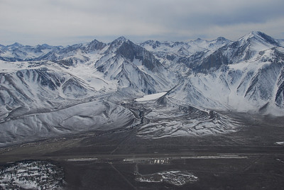 Mammoth Lakes airport at the base of the eastern side of the Sierras.  The airport elevation is 7,000 ft.  The peak on the right is Bloody Mountain, at 12,549 ft, and on the left is Mount Morrison, rising to 12,241 ft.  Photo taken from about 11,000 ft altitude.