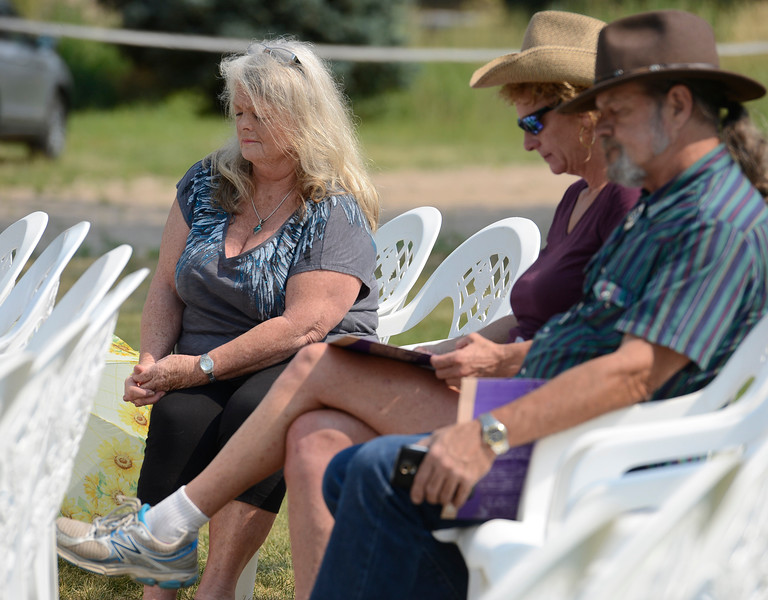 Deb Watts, left, a survivor of the 1976 Big Thompson flood, shares a moment of silence with others Friday, July 29, 2016, at Sylvan Dale Guest Ranch west of Loveland. Watts, her ex-husband, her three week-old baby boy and her 7 year-old daughter survived the flood but her 3 year-old son, Aaron, died in the 1976 flood. People gathered to commemorate lives lost and listen to weather and public safety experts discuss flood safety in Colorado, describe improvements in weather forecasting and compare the two major flood events of 1976 and 2013.  (Photo by Jenny Sparks/Loveland Reporter-Herald)