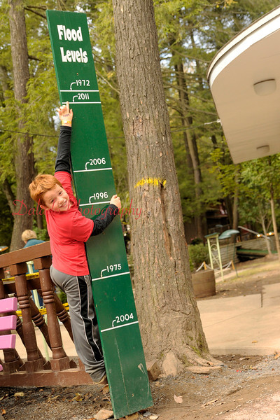 Jeremy Calo, 7, of Marlton, N.J., steps on a fence to reach the flood mark reached on Sept. 08, 2011, at Knoebels Amusement Resort Saturday, Sept. 17.