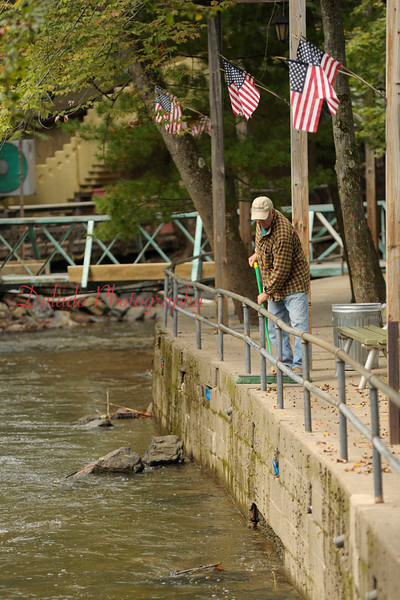 Mryon Chowka clears a sidewalk near the Grand Carousel of debris on Friday, Sept. 16.