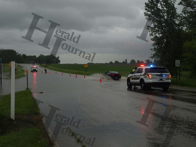 McLeod County Sheriff's deputies allowed traffic to pass through flooded road in one lane prior to closing the road June 19.