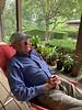 Bob Diebold, on veranda, W side of courtyard behind him