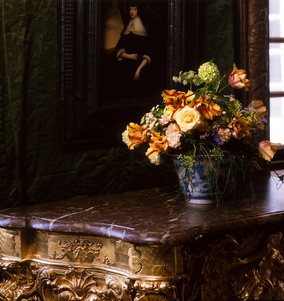 Interior detail of Spring flowers in a vase displayed on a gilded Baroque marble top pier table in Het Loo Palace, a Dutch Baroque royal palace and gardens