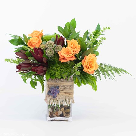 Blue and green hydrangea arranged with roses and succulents in a burlap wrapped vase