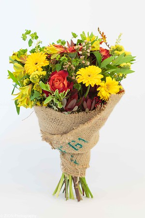 A burlap wrapped bouquet of daisies, roses and other assorted flowers.