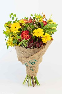 A burlap wrapped bouquet of daisies, roses and other assorted flowers