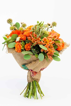 A burlap wrapped bouquet of orange roses with other leafy greens