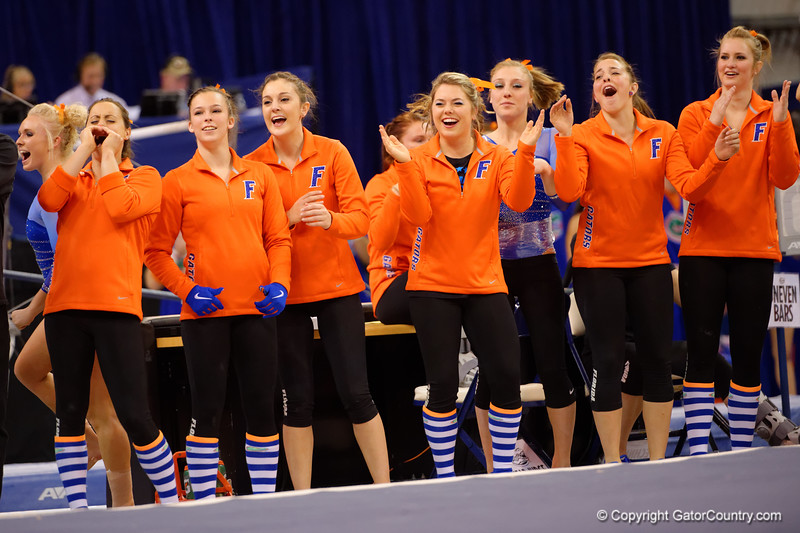The Gators cheer on as they compete in the floor exercise.  Florida Gators Gymnastics vs Georgia Bulldogs.  January 30th, 2015. Gator Country photo by David Bowie.
