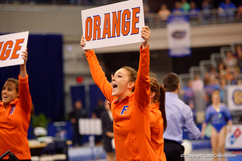 Florida Gators gymnast Bianca Dancose-Giambattisto holds up an orange sign to get the crowd involved.  Florida Gators Gymnastics vs Georgia Bulldogs.  January 30th, 2015. Gator Country photo by David Bowie.