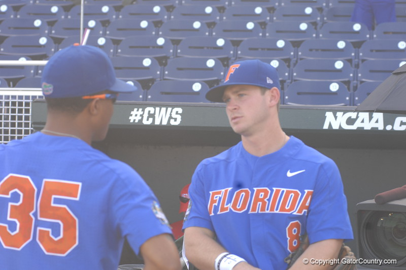 Andrew Baker and Deacon Liput talk in the dugout.