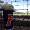 A bat weight and rosin bag sitting inside the Gators first base dugout.