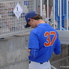 Florida Gators pitcher Jackson Kowar signs a baseball for a young fan.