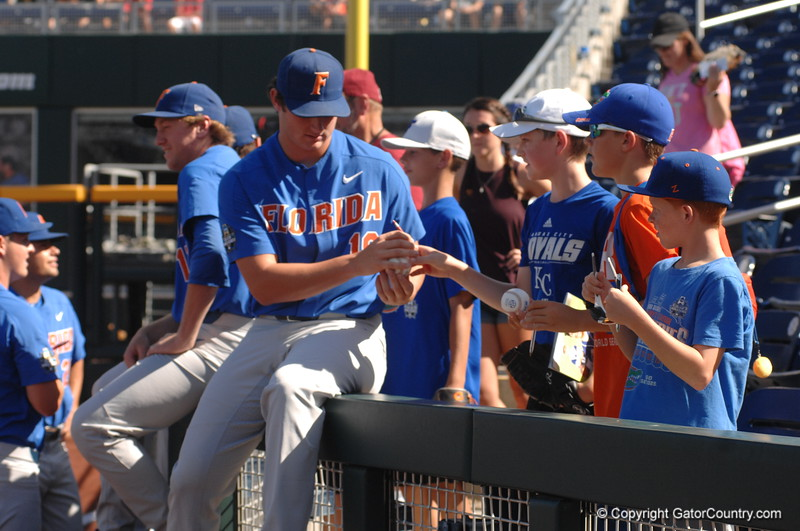 Florida Gators pitcher Tyler Dyson signs a baseball for a fan before the Gators game against Louisville.