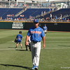 Kevin O'Sullivan walking back to the dugout while his team warms up and throws before their game against Louisville