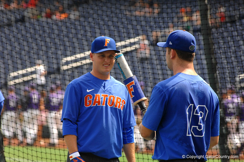 Freshmen Kirby McMullen and Austin Bodrato talk in between rounds during batting practice.