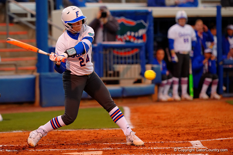 Florida Gators outfielder Kirsti Merritt drives the ball for a base hit in the first inning.  Florida Gators vs NC State Wolfpack.  February 13th, 2015. Gator Country photo by David Bowie.