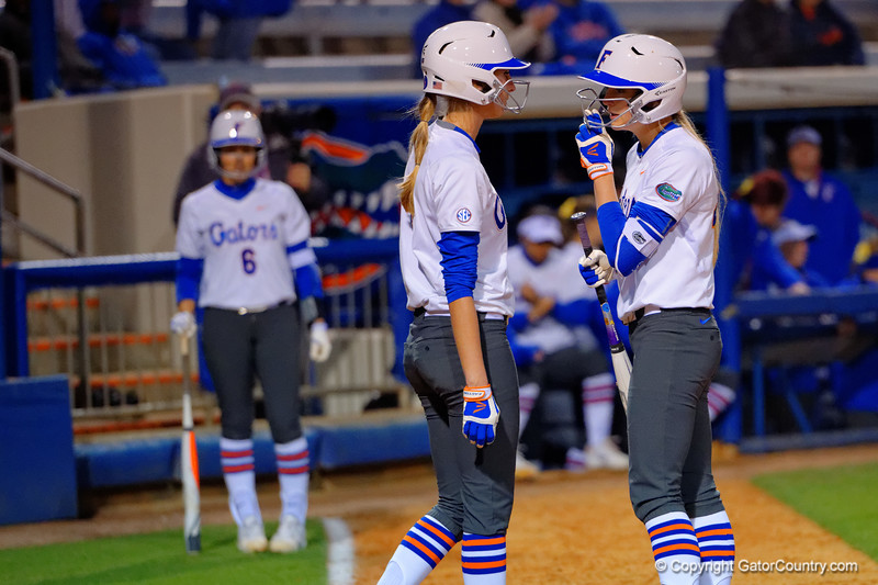Florida Gators catcher Aubree Munro comes out to talk with Florida Gators first baseman Taylor Schwarz about her at bat.  Florida Gators vs NC State Wolfpack.  February 13th, 2015. Gator Country photo by David Bowie.
