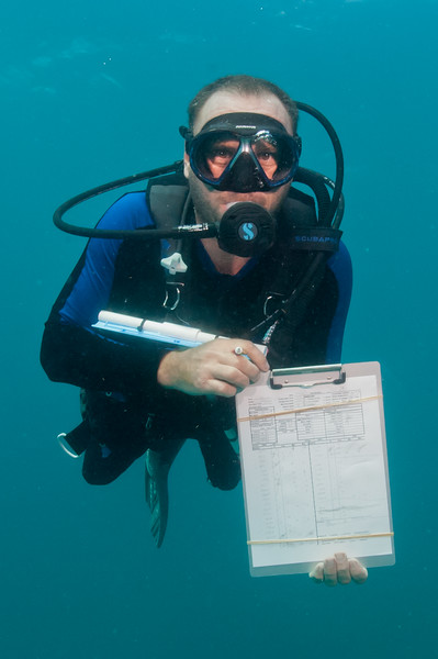 AN NPS SFCN Fisheries Biologist shows off his completed data sheet at the end of a survey dive in Biscayne.