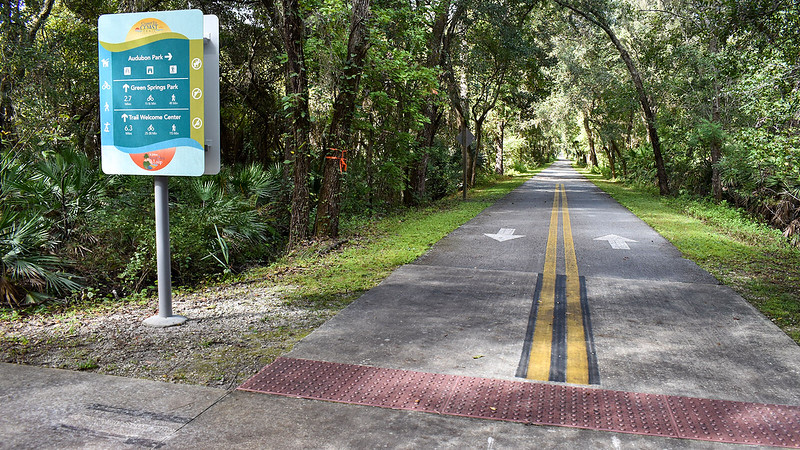 Colorful directional sign with bike path stretching beyond under trees