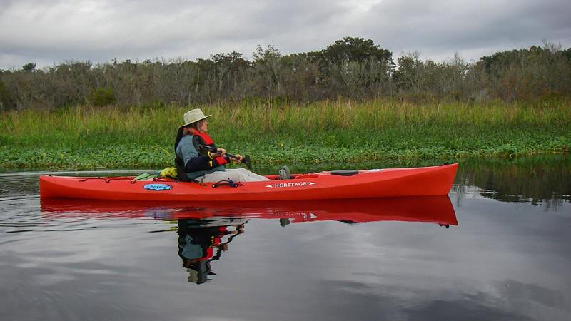 Woman in red kayak under overcast skies