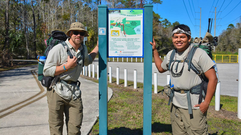 Two men with backpacks standing next to trail sign
