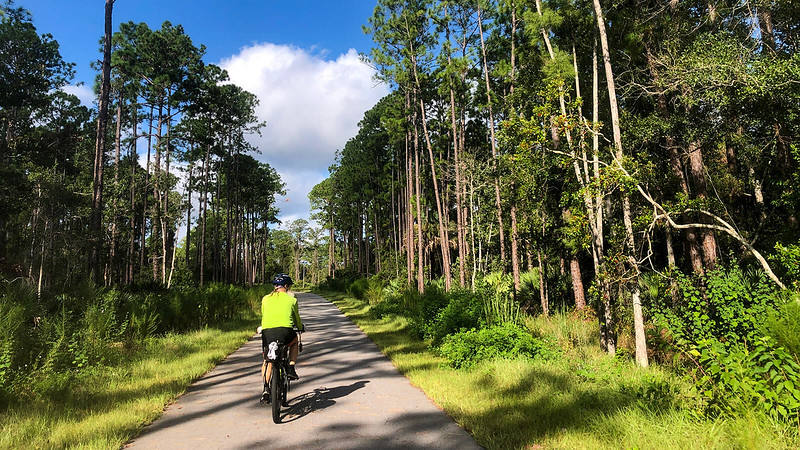 John riding along a tree lined bike path