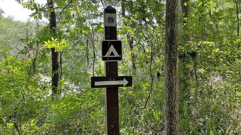 Trail sign with campsite symbol