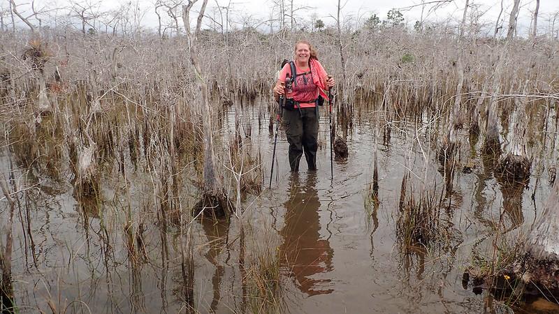 Woman standing in cypress swamp shin deep in water