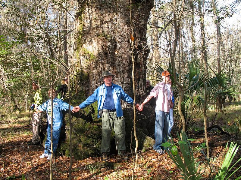 Big Oak base encircled by people holding hands