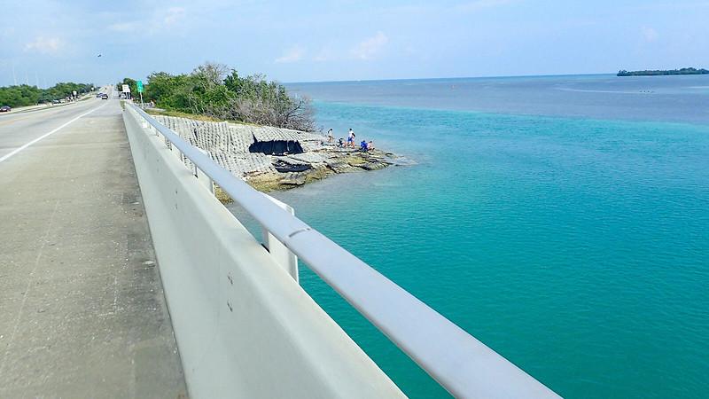 People at edge of aquamarine waters on island