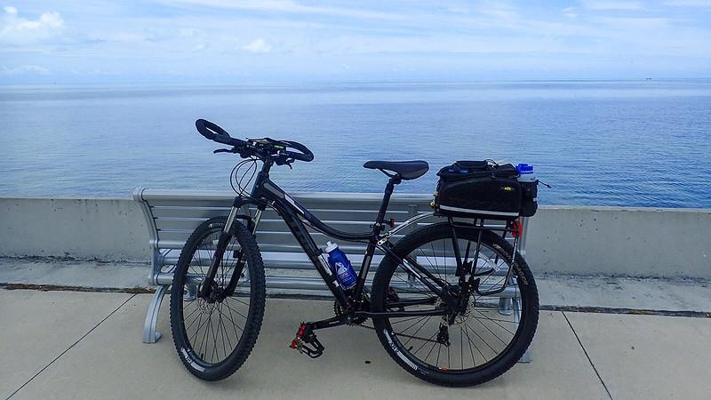 Bike leaning on bench next to ocean to horizon