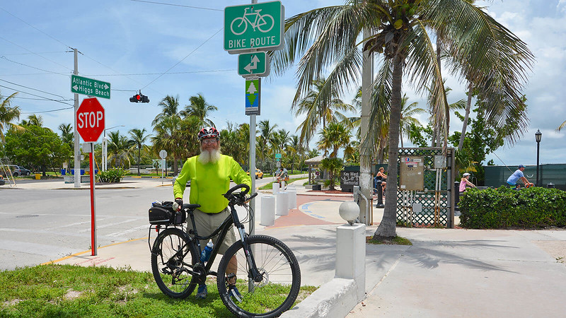 John in bright yellow shirt with mountain bike next to coconut palm tree